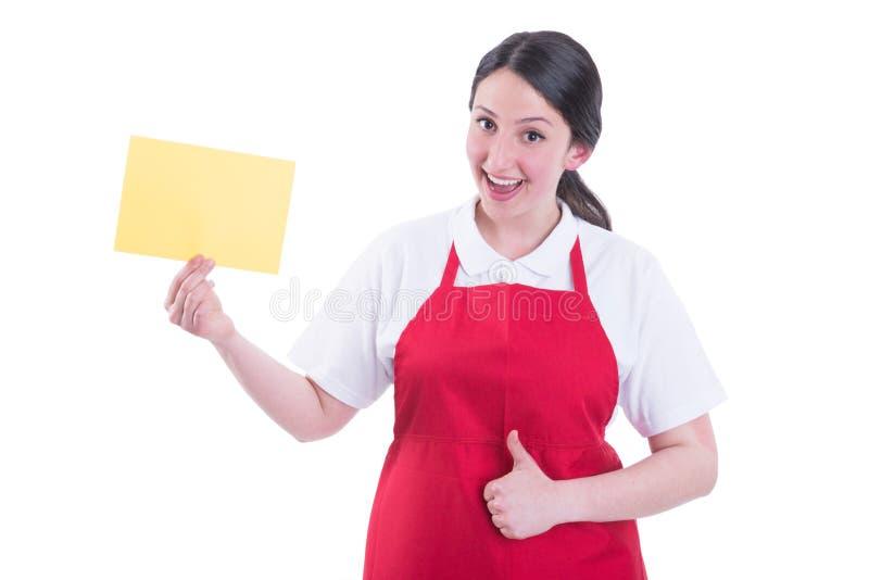 Vendeur féminin gai avec le thumbup de représentation de papier vide photos stock
