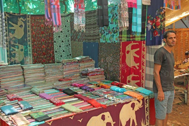 Vendeur indien d'homme sur le marché d'Anjuna, Goa, Inde Marchés indiens, le commerce Un stock de châles et d'étoles photos libres de droits