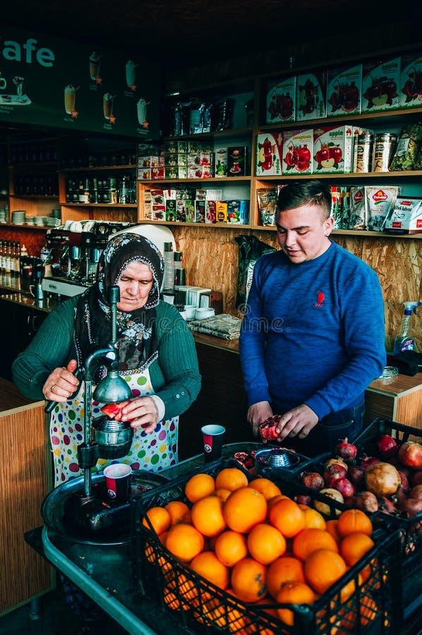 Vendeur local dans la boutique fraîche de jus, regard de film avec l'agrume et fruit à pépins photographie stock