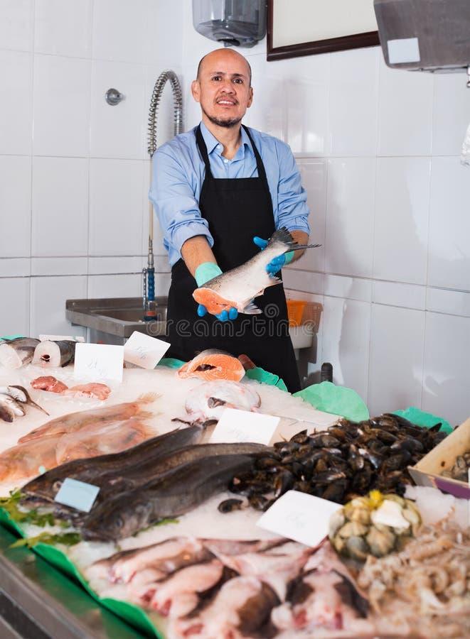 Vendeur mûr gai avec le poisson frais de offre de tablier photos libres de droits