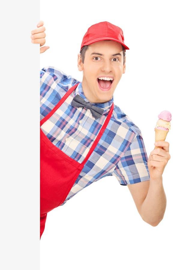 Vendeur masculin de crème glacée posant derrière le panneau photos stock