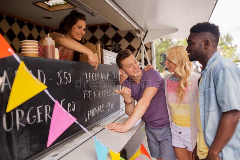 Vendeur montrant le menu aux clients au camion de nourriture image libre de droits