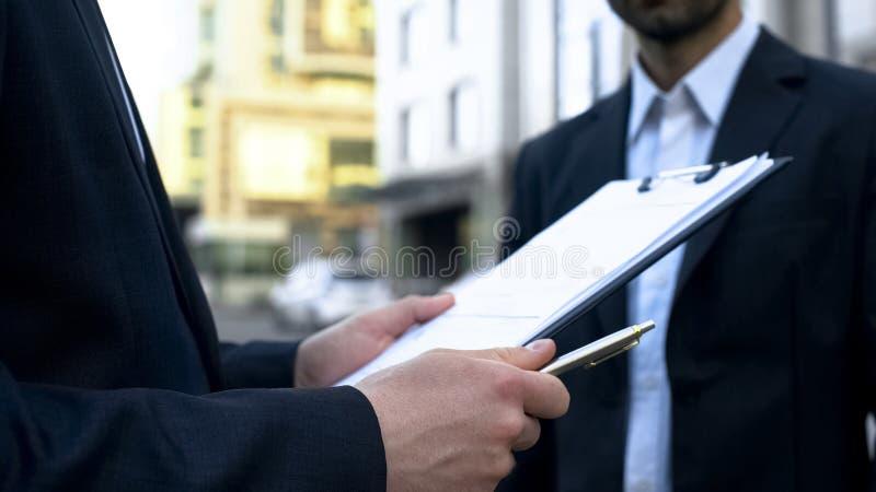 Vendeur regardant par la liste, recherchant le nom de l'automobile de achat de l'homme, affaire d'affaires photo libre de droits