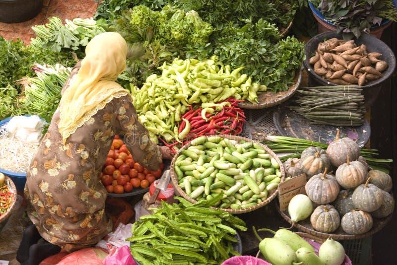 Vendeur végétal au marché humide image stock