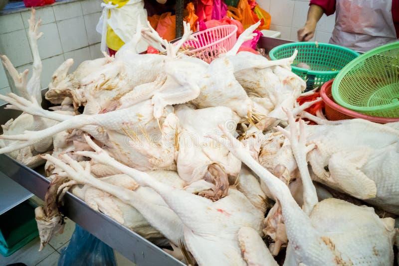 Vendeur vendant le poulet entier fraîchement abattu dans la stalle du marché image stock