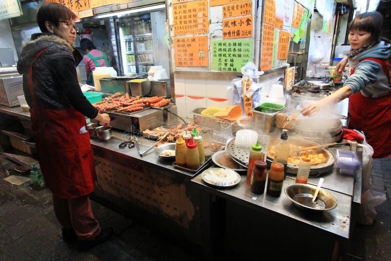 Vendeurs de rue vendant la nourriture la nuit au HK photographie stock libre de droits