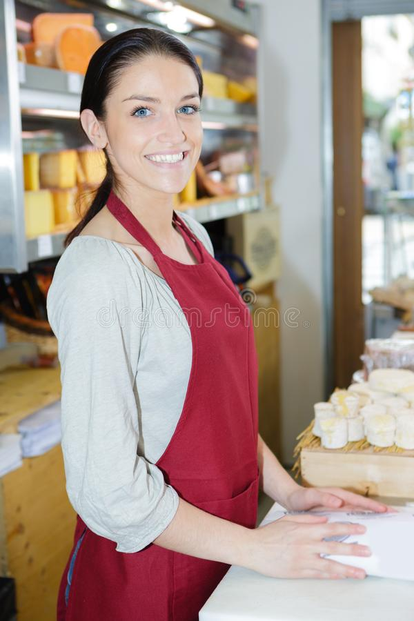 Vendeuse At Checkout Counter dans l'épicerie photographie stock