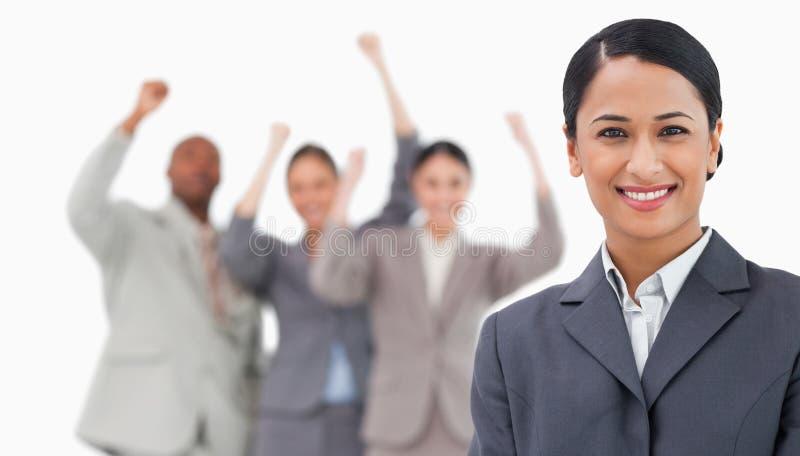 Vendeuse de sourire avec les collègues encourageants derrière elle photo libre de droits