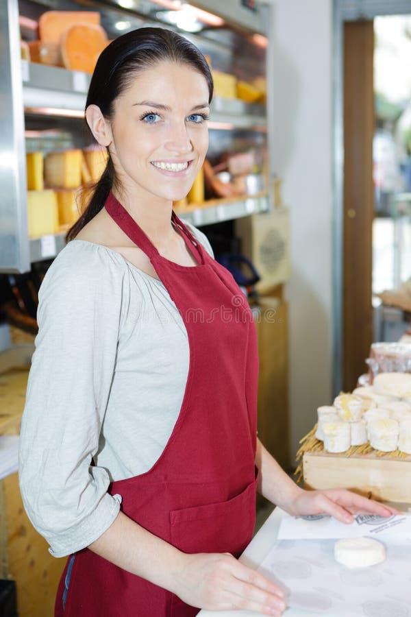 Vendeuse heureuse de portrait dans la boutique de fromage images libres de droits