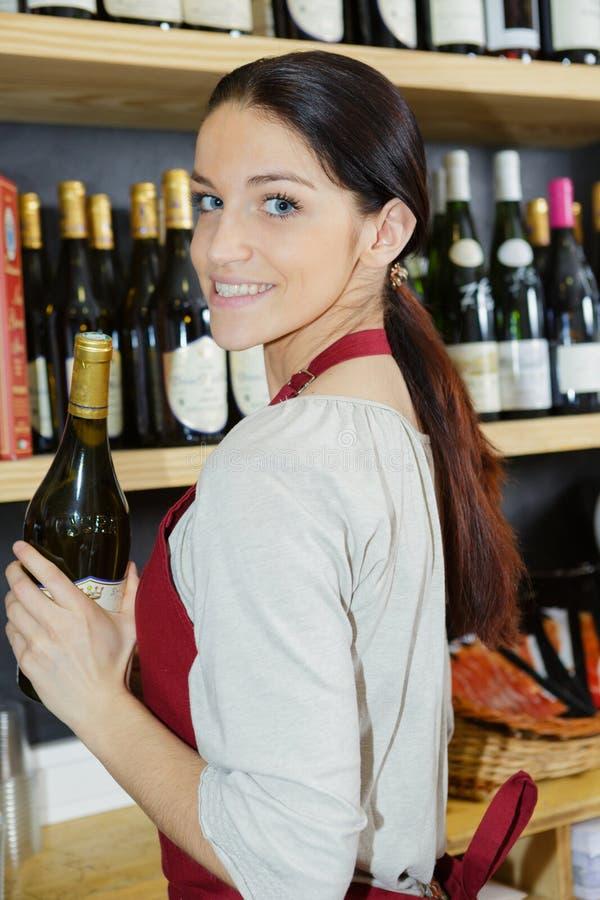 Vendeuse heureuse Standing Against Shelves dans la boutique de vin image stock