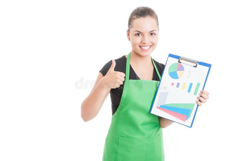Vendeuse heureuse tenant le presse-papiers avec des diagrammes photos stock