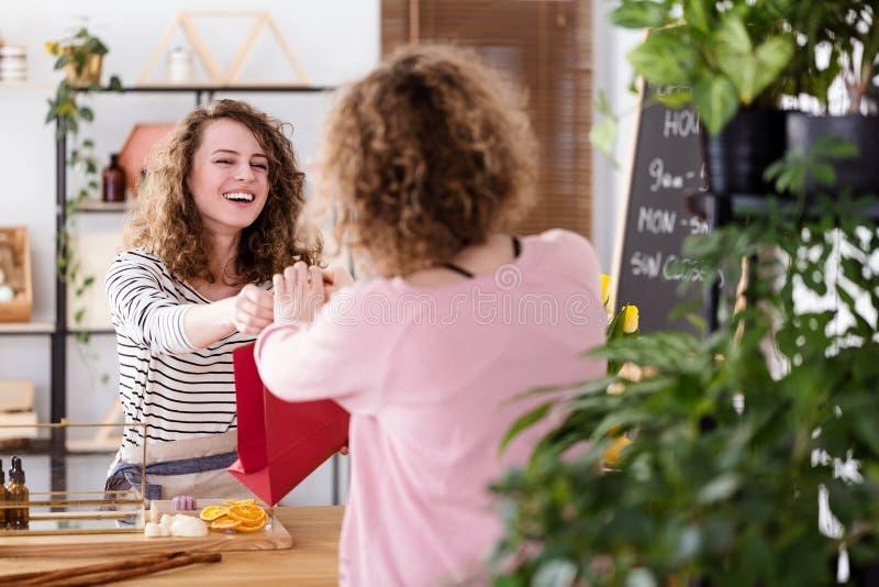 Vendeuse heureuse vendant des produits de soins de la peau photographie stock