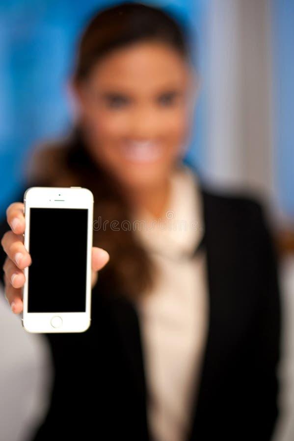 Vendeuse montrant le mobile nouvellement lancé images stock