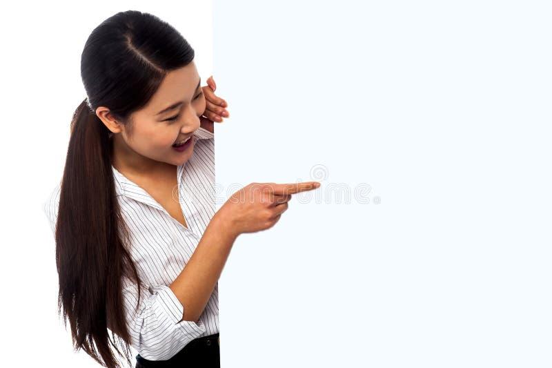 Vendeuse se dirigeant vers l'annonce sur le panneau d'affichage image stock