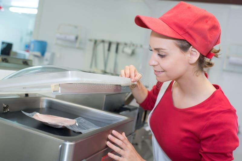 Vendeuse travaillant avec de la viande coupée en tranches au supermarché images libres de droits