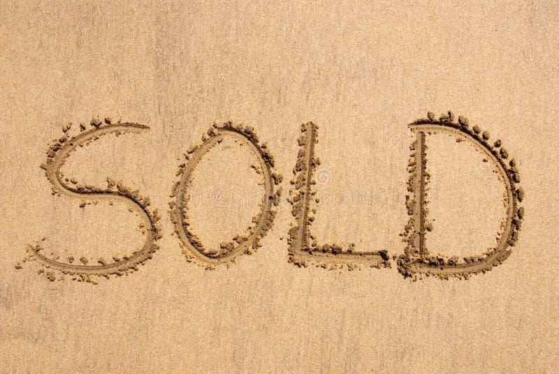 ?Vendido? escrito na areia imagem de stock royalty free