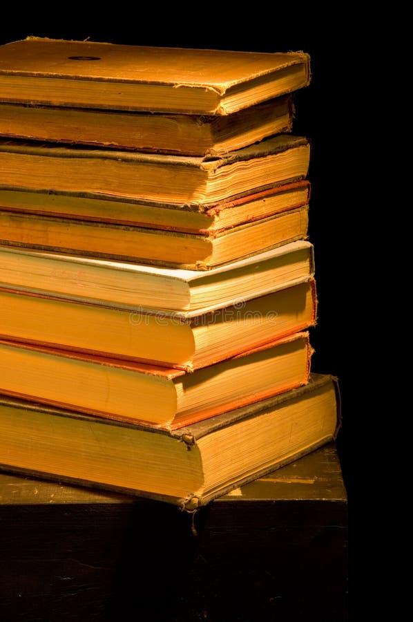 Vendimia, pila de la antigüedad de los libros pintados con la luz fotos de archivo