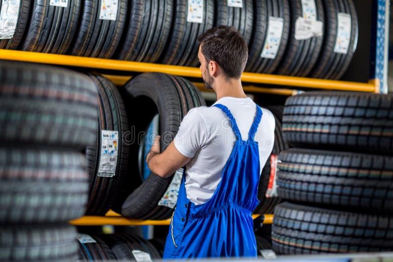 Vendita del meccanico una nuova gomma per l'automobile fotografia stock libera da diritti