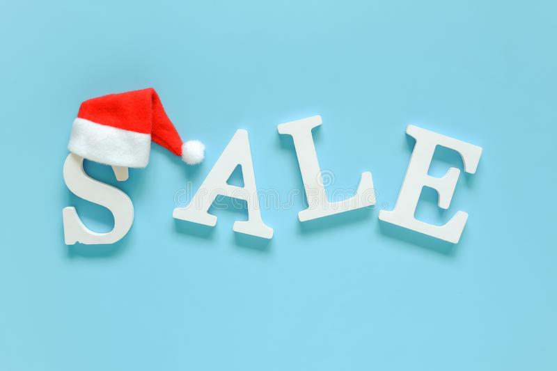 VENDITA del testo dalle lettere e dal cappello bianchi di Santa Claus su fondo blu Nuovo anno di concetto dello spazio della copi immagini stock libere da diritti