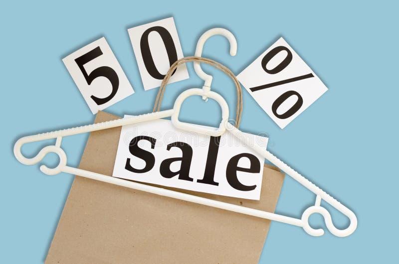 Vendita di 50% borsa e gancio della carta kraft su fondo blu fotografia stock