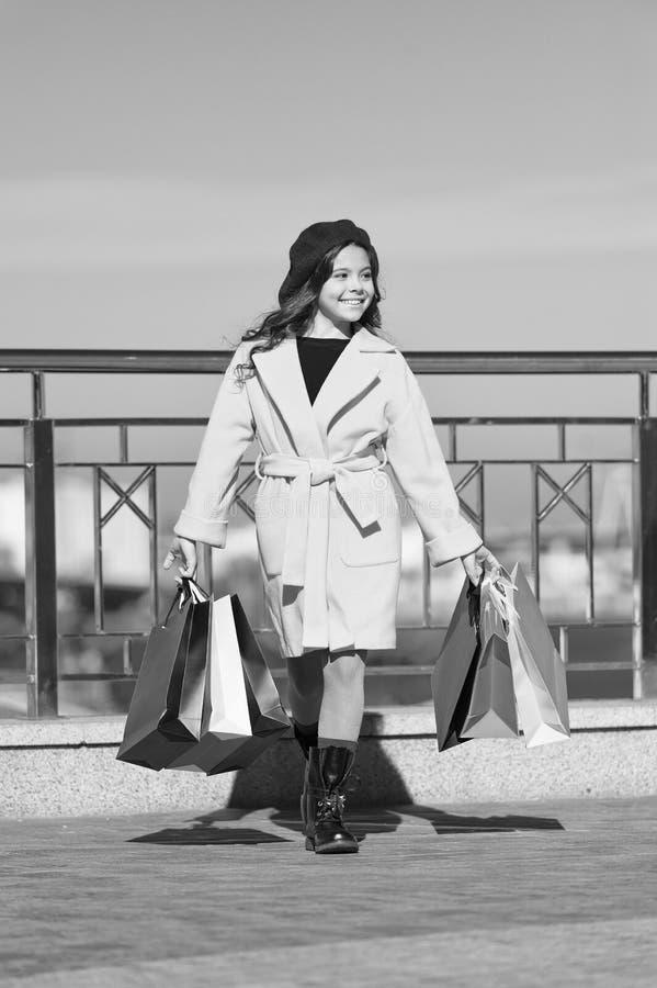 Vendite della primavera Sguardo di modo del bambino Tendenza di autunno Giorno di acquisto Bambina felice Bambina con i sacchetti immagini stock