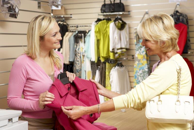 Vendite di aiuto con il cliente nella memoria di vestiti fotografia stock libera da diritti