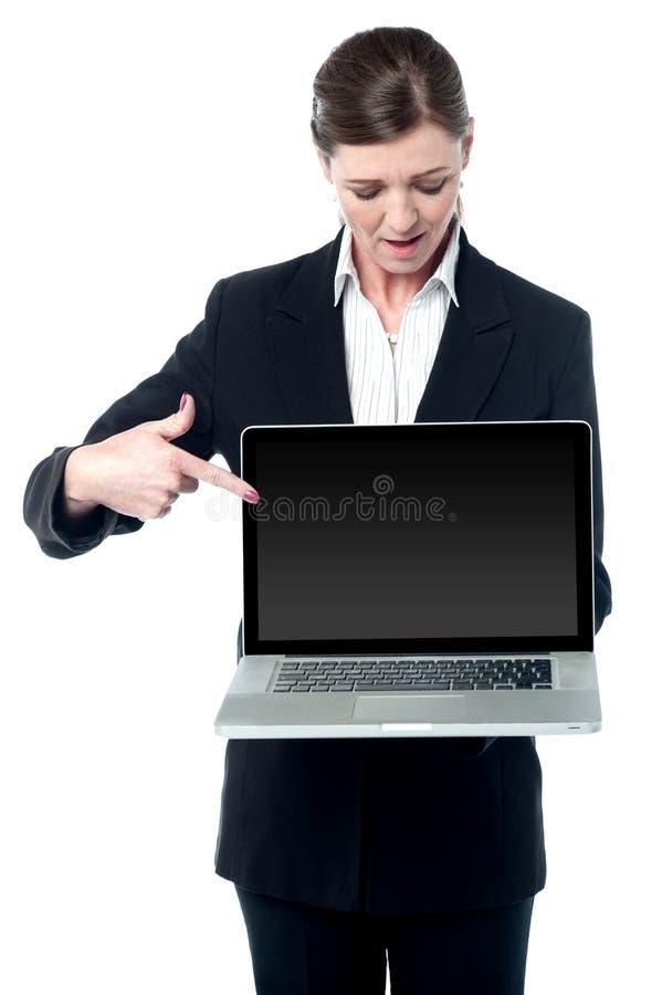 Venditora che indica allo schermo di nuovo computer portatile fotografia stock libera da diritti