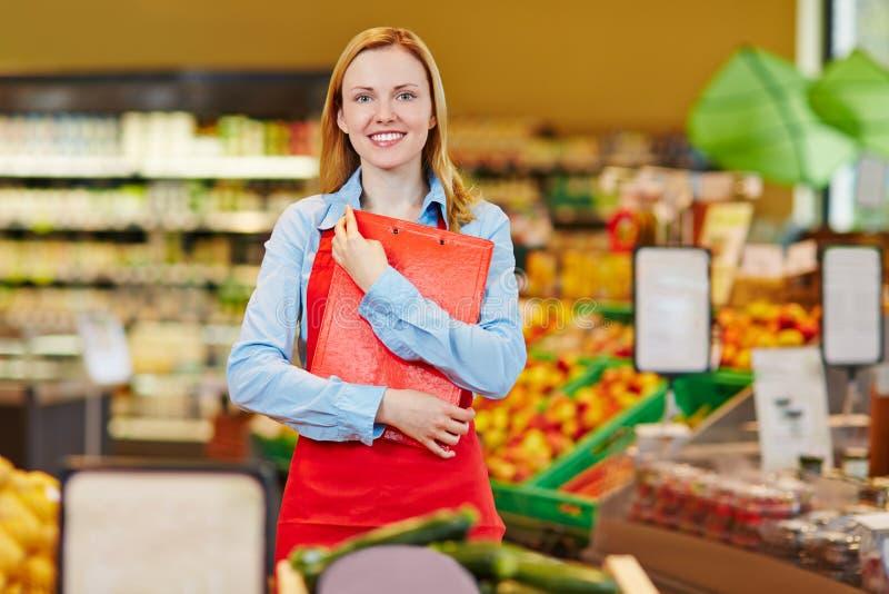 Venditora sorridente in supermercato immagini stock
