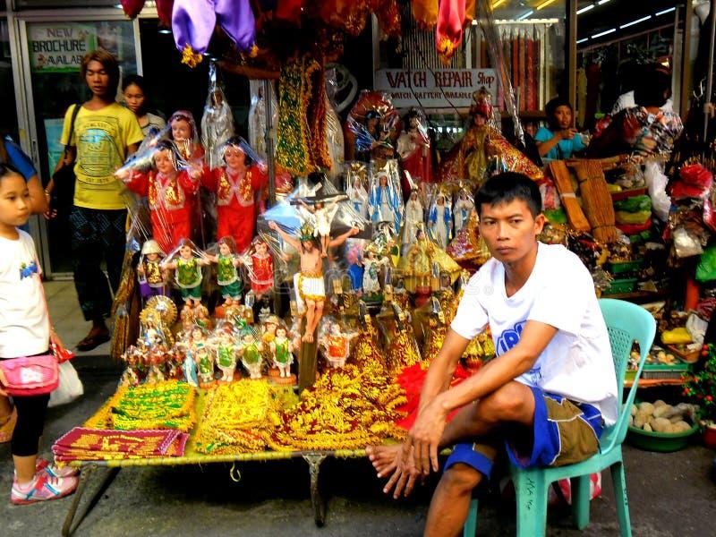 Venditore ambulante asiatico che vende gli oggetti religiosi differenti fuori della chiesa di quiapo in quiapo, Manila, Filippine  fotografie stock libere da diritti