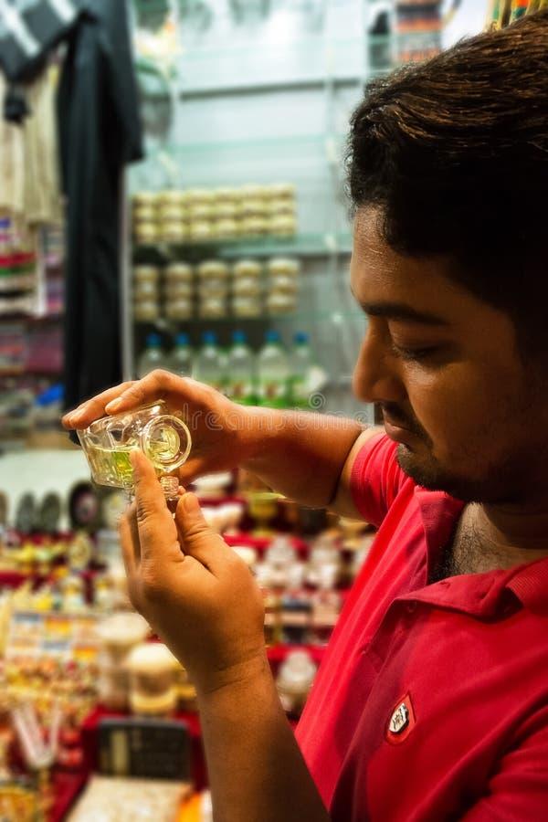 Venditore che riempie una piccola bottiglia di profumo nel souk di Mutrah in Muscat fotografia stock