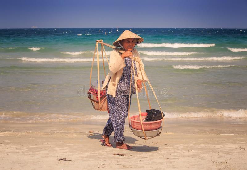 Venditore della donna anziana del primo piano con Yoke Stands sulla spiaggia dell'oceano immagini stock libere da diritti