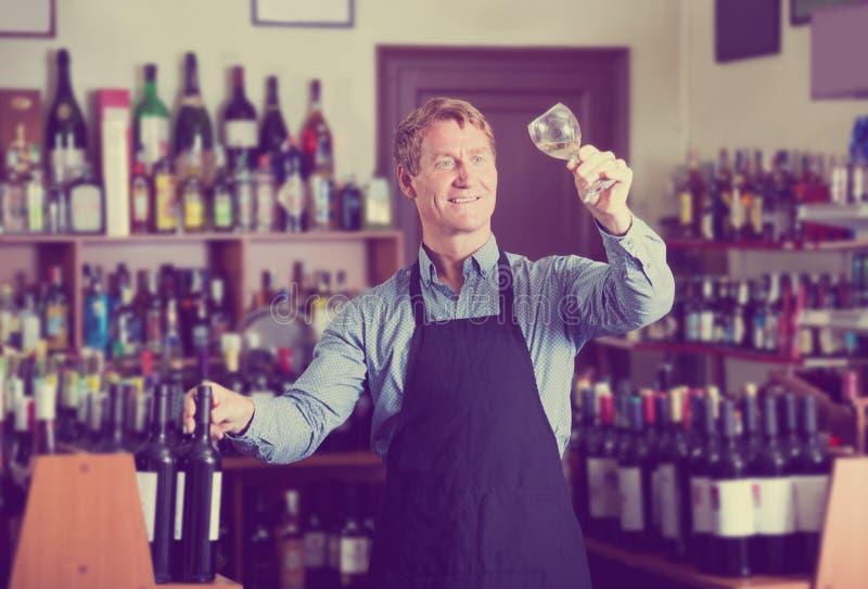 Venditore maschio che promuove provare vino prima dell'acquisto fotografie stock