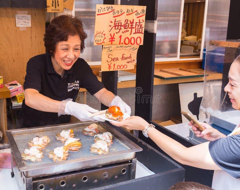 Venditore sorridente felice della donna che vende il piatto dei frutti di mare al cliente immagini stock