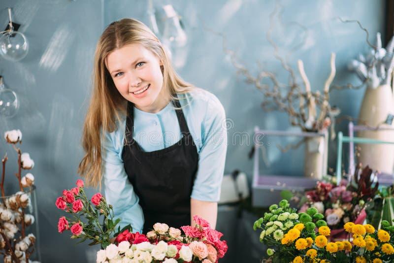 Venditore uscente e felice che offre composizione floreale immagini stock
