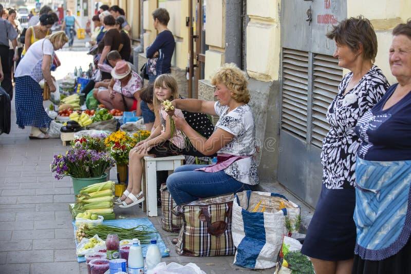 Venditori del mercato di strada di mattina con le verdure nostrane fresche nel centro urbano Leopoli, Ucraina Donne che vendono a fotografia stock