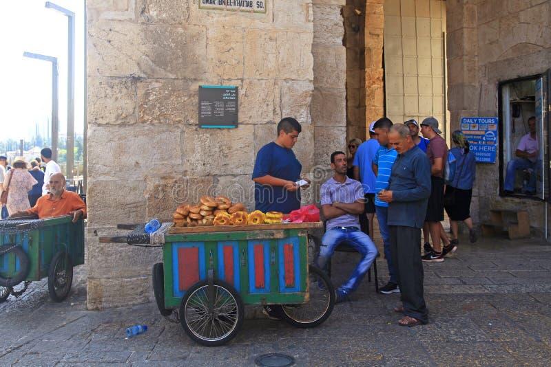 Venditori del pane tipico del bagel con il carretto vicino al portone di Giaffa in immagine stock libera da diritti