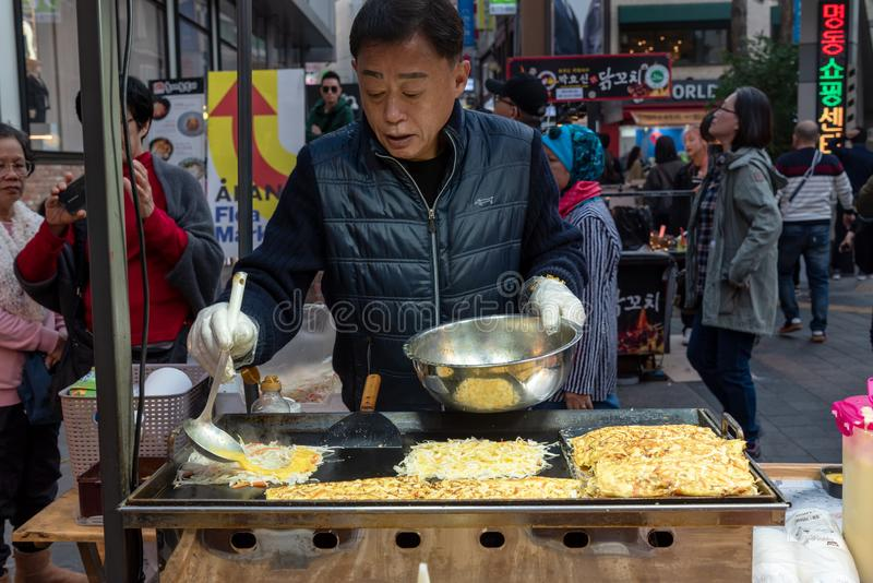 Vendor cooking vegetable pancake at food stall in Myeongdong street market stock photography