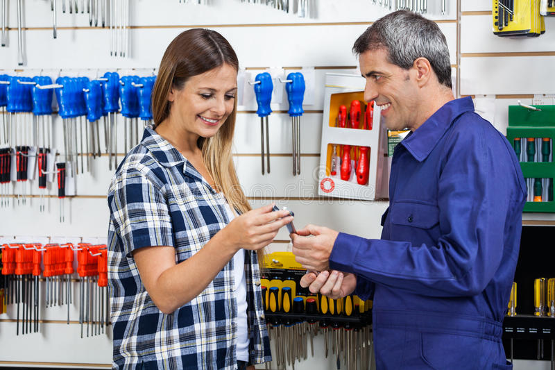 Vendor Giving Wrench To Customer In Shop royalty free stock photos