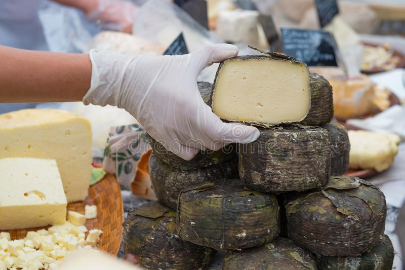 Vendor hands holding cheese on the market royalty free stock images