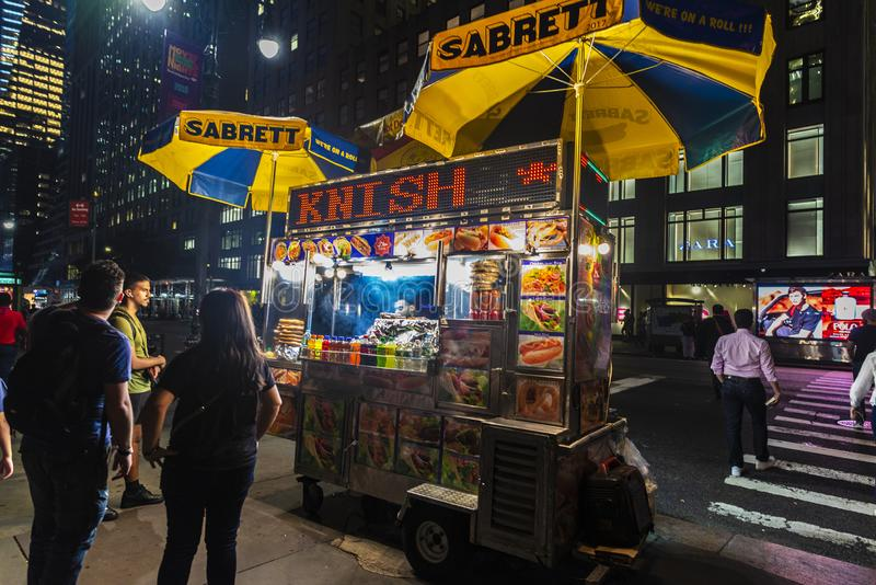 Vendor in its food truck at night in New York City, USA. New York City, USA - August 1, 2018: Vendor cooking in his food truck with people around at night in royalty free stock image