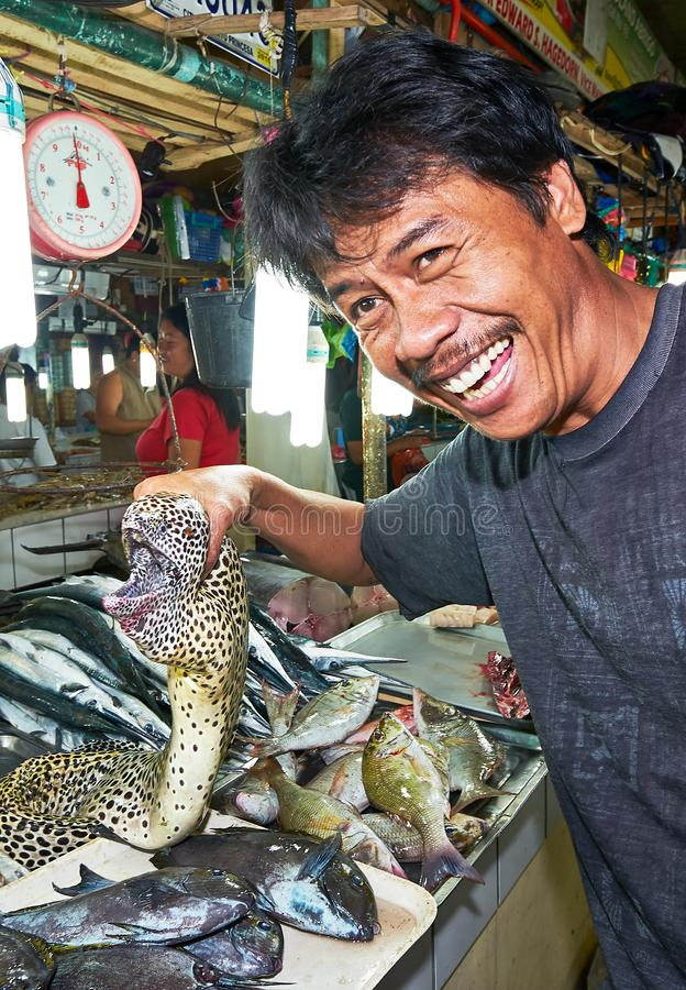 Vendor makes fun and is holding a moraine fish royalty free stock images
