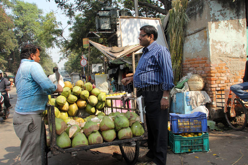 Vendor sells coconuts. On the outdoor market on November 28, 2012 in Kolkata. Only 0.81% of the Kolkata`s workforce employed in the primary sector agriculture royalty free stock image