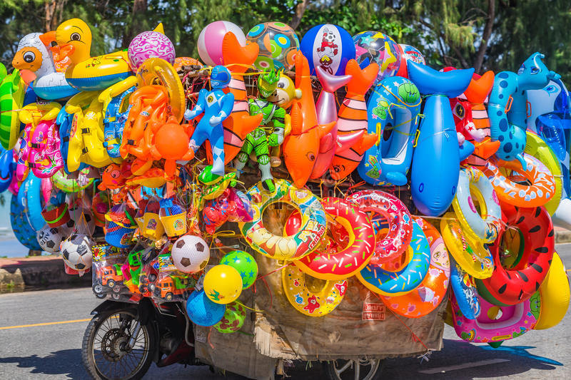 A vendor sells colorful beach toys and floats. A vendor sells very colorful beach toys and floating tubes etc at a beach in Thailand royalty free stock image