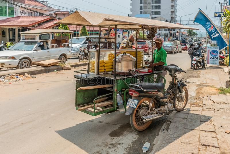 Vendor sells corn on the cob from tricycle in Sihanoukville Cambodia. Sihanoukville, Cambodia - March 15, 2019: Ambulant vendor sells corn on the cob from his royalty free stock images