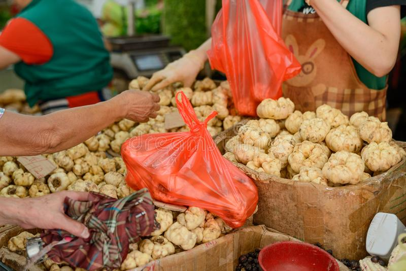 Vendor sells edible lily bulbs. Food market in China royalty free stock images
