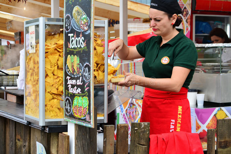 Vendor sells Mexican food. CLUJ-NAPOCA, ROMANIA - JULY 9, 2016: Vendor woman sells Mexican food at the Street Food Festival Cluj royalty free stock image