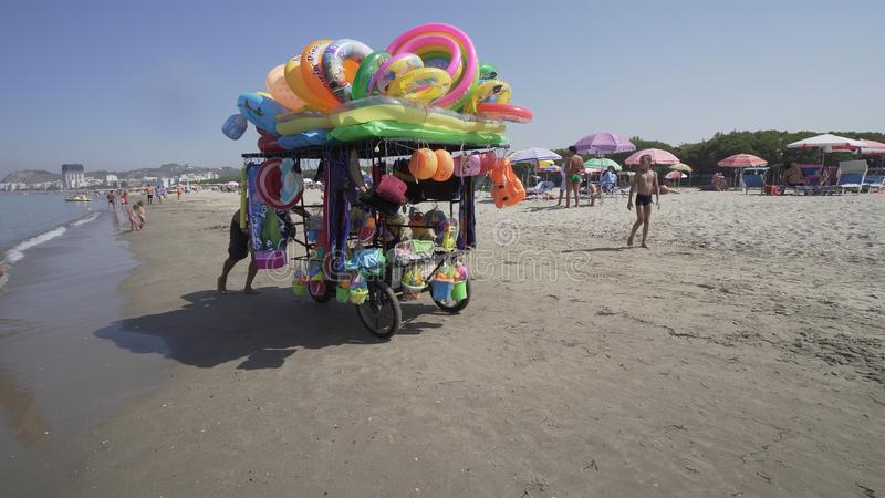 Vendor sells swimsuit and toys to children on the beach. Durres, Albania - circa Aug, 2017: Vendor sells swimsuit and toys to children on the beach, cinematic royalty free stock image