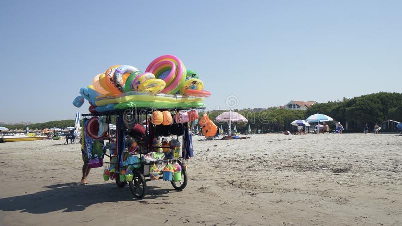 Vendor sells swimsuit and toys to children on the beach. Durres, Albania - circa Aug, 2017: Vendor sells swimsuit and toys to children on the beach, cinematic royalty free stock photography