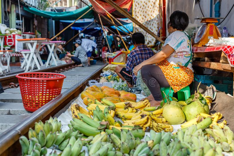 Vendors at famous Maeklong railway market selling fruit and vegetables at railway tracks, Samut Songkhram province, Thailand stock images
