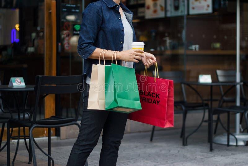 Vendredi noir Femme avec la tasse de café tenant des sacs à provisions photographie stock